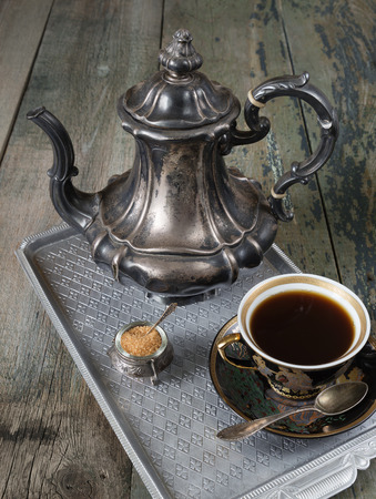 antique: Black coffee in vintage cup and antique silver coffee pot on a old dark wooden boards
