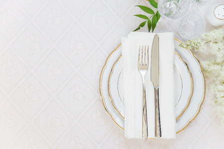 Top view of the beautifully decorated table with white plates, crystal glasses, linen napkin, cutlery and white flower on luxurious tablecloths, with space for text