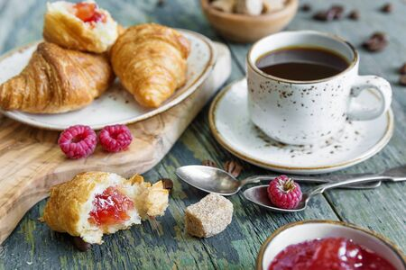 breakfast cup: A light breakfast consisting of a cup of black coffee and croissants with a stuffing from raspberry jam