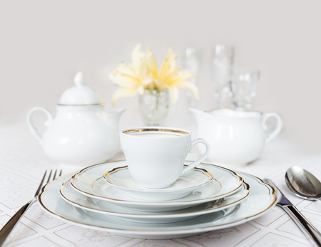 celebration event: Beautifully decorated table with white plates, crystal glasses, linen napkin, cutlery and lily flowers on luxurious tablecloths