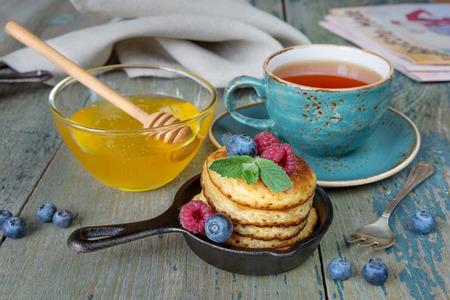 Breakfast of pancakes in cast-iron frying pans, fresh berries, honey and black tea in rustic style Standard-Bild