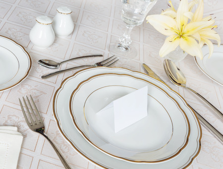entertainment event: Beautifully decorated table with white plates, crystal glasses, cutlery and flowers on luxurious tablecloths, with guest card