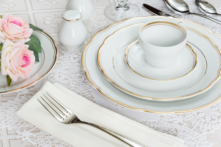 Beautifully decorated table with white plates, crystal glasses, linen napkin, cutlery and rose flowers on luxurious tablecloths