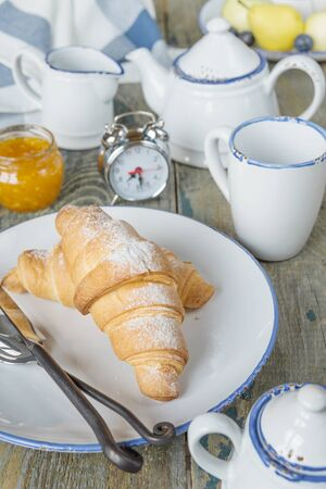 light breakfast: A light breakfast consisting of a cup of tea and croissants with a jam