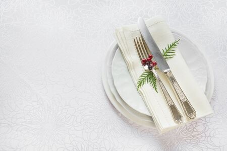 christmas menu: Silver knife and fork, and red holly berries and green thuja branches lie on the white porcelain plate, which is located on a table covered with a white tablecloth, top view Stock Photo