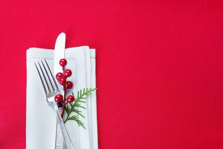 comida de navidad: cuchillo y tenedor de plata, acebo y bayas rojas y verdes rama tuya se encuentran en la servilleta de lino blanco, que se encuentra sobre una mesa cubierta con un mantel rojo, vista desde arriba Foto de archivo