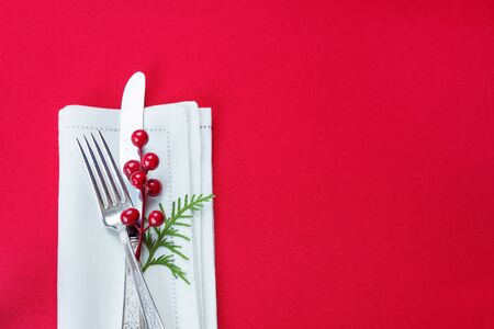 and to celebrate: Silver knife and fork, and red holly berries and green thuja branch lie on the white linen napkin, which is located on a table covered with a red tablecloth, top view