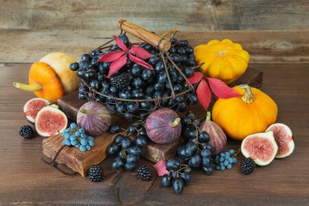 blue vintage background: Black grapes in a vintage metal basket with wooden handle and ripe figs, red raspberries, orange pumpkin and blackberries with autumn leaves on the wooden background