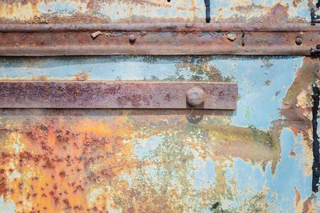 crackles: Old rusty metal surface with with two metal strips, blue paint flaking and cracking texture