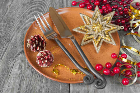 faience: Still  knife and fork handmade lie on the brown faience plate, as well as golden star and red holly berries which is located on a old wooden table
