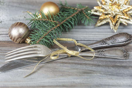 golden ball: Vintage knife and fork tied with golden ribbon, Christmas balls and star and green spruce branch on the old table Stock Photo