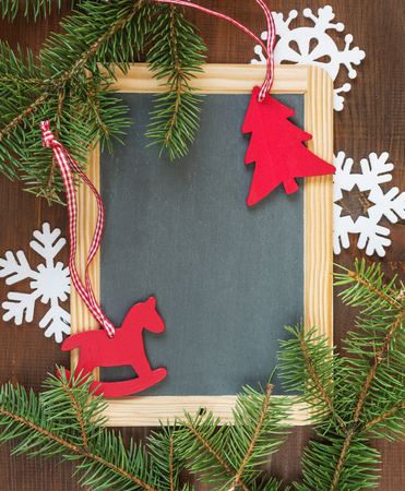 holiday ornament: Blank chalkboard surrounded by green fir branches, white felts snowflakes and red rocking horse and spruce