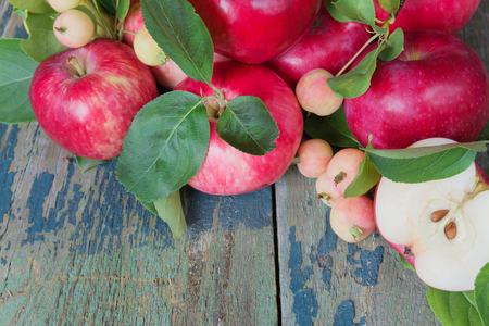 gardening: Many red apples with green leaves and half of apple on the old wooden table Stock Photo
