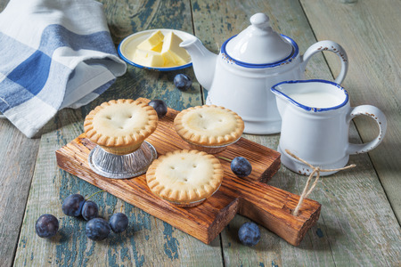 creamer: Three small enclosed cake with plums, butter and a creamer and sugar bowl in vintage style