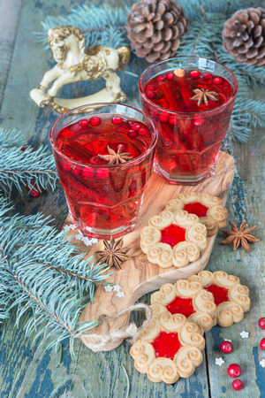 christmas tree branch: Christmas table - two glasses of red hot mulled wine with spices and cowberries and cookies with jam, surrounded by fir branches and cones