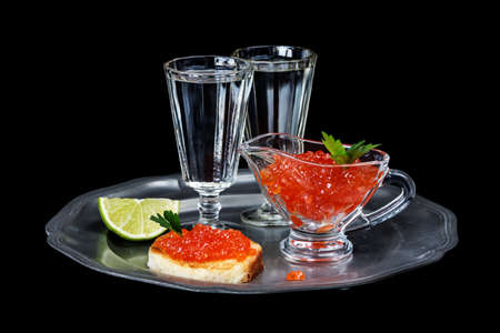 sandwiche: Sandwiches with red caviar and two glasses of vodka on a pewter plate isolated at black
