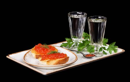 sandwiche: Sandwiches with red caviar and two glasses of vodka on a porcelain plate isolated at black Stock Photo