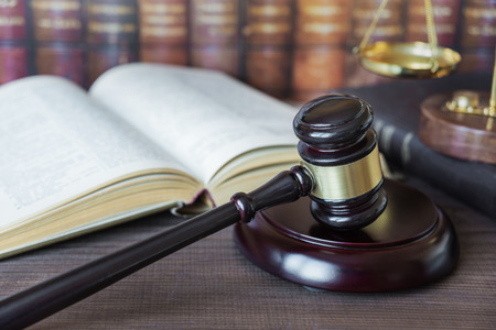 civil law: Wood gavel, soundblock, scales and opened old book against the background of a row of antique books bound in leather