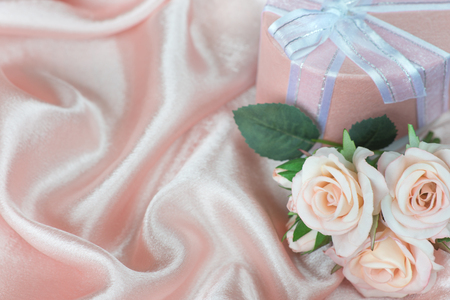 gift bow: Pink roses and gift box with bow on a background of the silk fabric Stock Photo