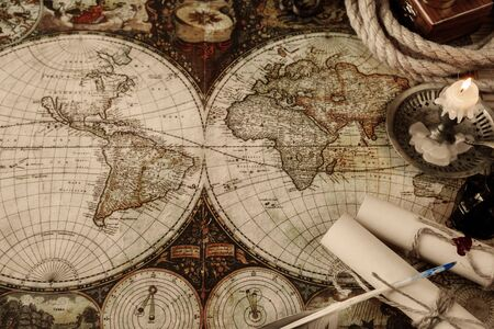 cartography: Burning candle, scrolls of paper, pen, ink, and the ships rope located on the background of old map Stock Photo