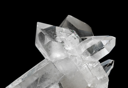 twinning: Cluster of several transparent rock crystals close-up, isolated on a black background