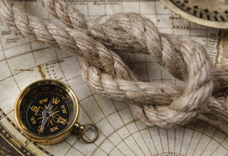 Compass and marine knot located on the background of old map Stock Photo