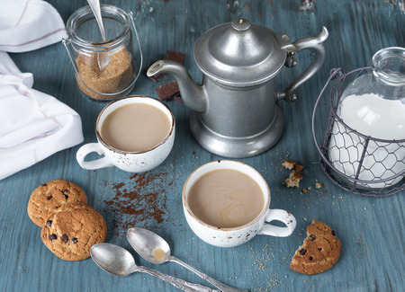 homemade style: Family breakfast - two cups of coffee with milk espresso and homemade oatmeal cookies with chocolate on a blue wooden vintage table, rustic style, top view