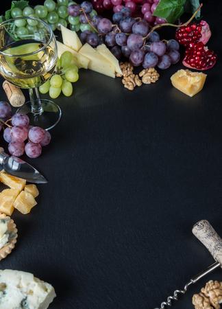 grapes: vino blanco, varios tipos de queso, nueces y uvas en un fondo de piedra de pizarra negro Foto de archivo