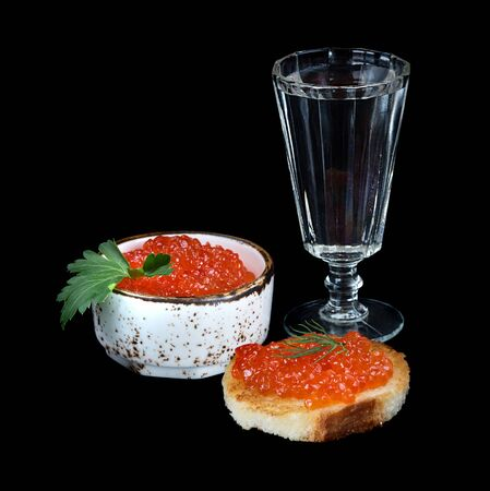 sandwiche: Sandwich with fish eggs and glass of vodka isolated on black background
