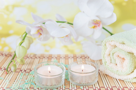 mat like: Spa concept: bath towels, two lighted candles and a branch of white orchid