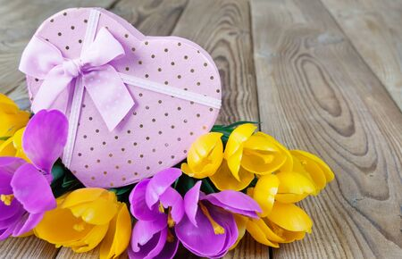 unpainted: Bouquet of yellow and purple crocuses and pink gift box in the shape of a heart, tied with ribbons, on an unpainted wooden surface Stock Photo