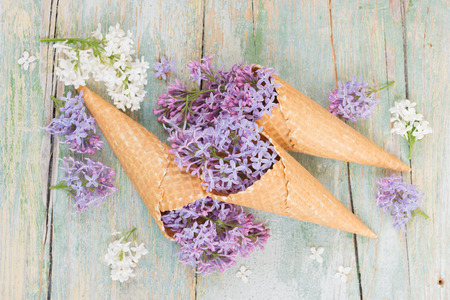 Spring still life with purple lilac flowers in waffle cones on the background of old boards