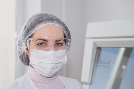 protective clothing: Woman scientist in a white protective clothing preparing for the experiments in the laboratory looking directly