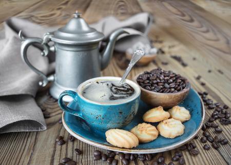 Blaue Tasse schwarzen Kaffee, Kekse und Kaffeekanne von Leinentuch umgeben, Zuckerstücke und Kaffeebohnen auf alten Holztisch