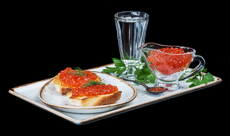 sandwiche: Sandwiches with fish eggs and glass of vodka on a porcelain plate isolated on black background