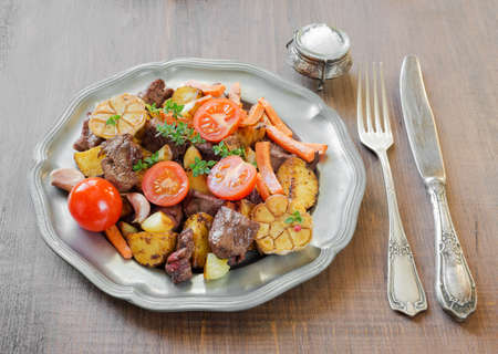 pewter: Roast venison meat with vegetables on a vintage pewter plates and old cutlery on a wooden table Stock Photo