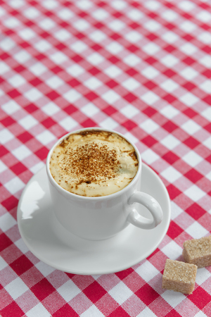 crema: Black coffee with crema in a white porcelain cup and cane sugar on a background of red and white checkered cloth