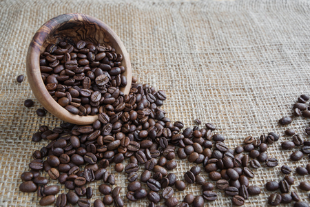coffee spill: Coffee beans spill out of a wooden bowl on the background of rough burlap