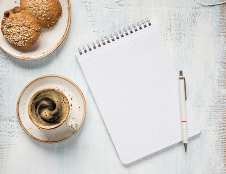 oatmeal cookie: Black coffee with crema in vintage porcelain cup,  checkered notepad; pencil and oatmeal cookie on a light wooden background, top view Stock Photo