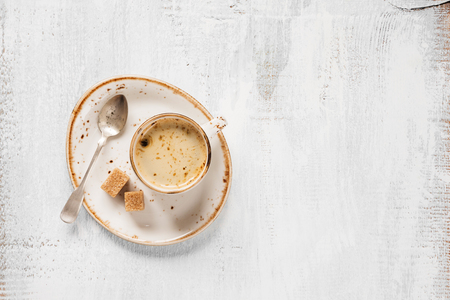 crema: Black coffee with crema in vintage porcelain cup and cane sugar on a light wooden background, top view