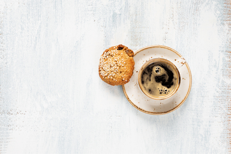 oatmeal cookie: Black coffee with crema in vintage porcelain cup and oatmeal cookie on a light wooden background, top view Stock Photo