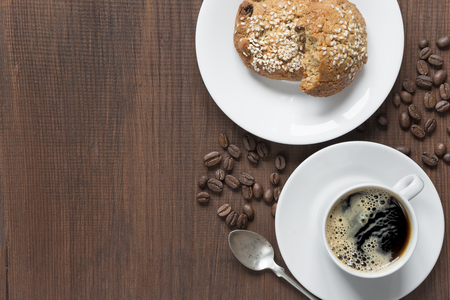 crema: Black coffee with crema in white porcelain cup and oatmeal cookies on a dark wooden background, top view