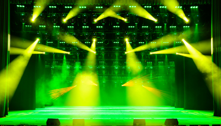 dramatics: Illuminated empty concert stage with green and yellow light and stage fog