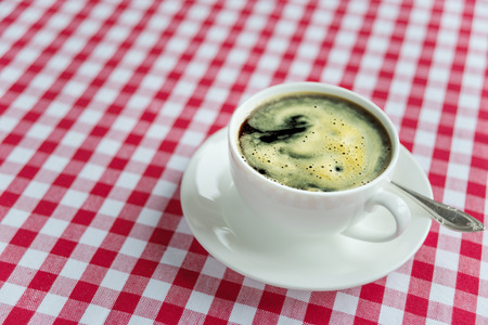 crema: Black coffee with rich crema in a white porcelain cup on a background of red and white checkered cloth