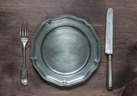 Vintage pewter plate, fork and knife on old dark wooden board Standard-Bild