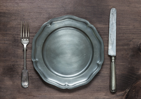 pewter: Vintage pewter plate, fork and knife on old dark wooden board Stock Photo