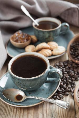 Twee blauwe kopjes zwarte koffie, koekjes en suiker stukjes omgeven door linnen doek op oude houten tafel