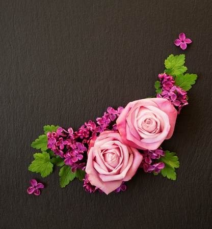 Decorative composition consisting of pink roses, violet lilac flowers and green leaves on a black slate. Flat lay, top view, overhead view