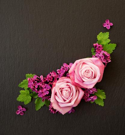 Decoratieve compositie bestaande uit roze rozen, violette lila bloemen en groene bladeren op een zwarte leisteen. Plat leggen, bovenaanzicht, bovenaanzicht