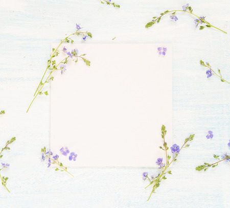 Scrapbooking page of wedding or family photo album, frame with fresh blue flowers on light wooden background; top view, flat lay, overhead view